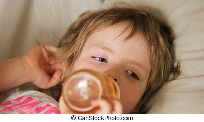 Child drinking juice form bottle. - The young girl lies on a...
