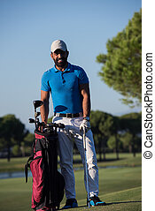 golfer portrait at golf course - handsome middle eastern...