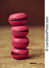 red macarons on a rustic wooden surface