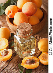 apricot kernel oil in a glass jar closeup. vertical -...