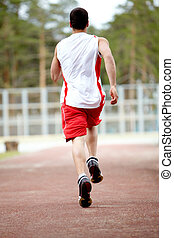 Workout - Rear view of energetic sportsman running down...