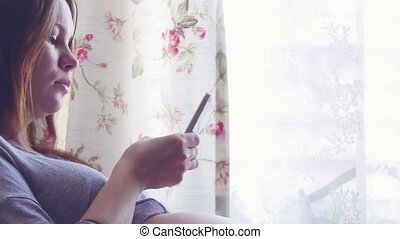 Pregnant woman using her smartphone at home sitting by the...