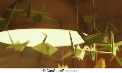 origami swans hanging under the lights as an ornamental decoration in interior. 1920x1080