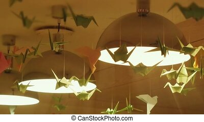 origami swans hanging under the lights as an ornamental...
