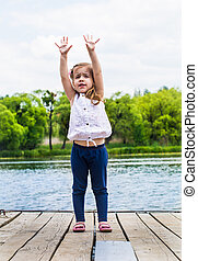 emotions of a little girl on beautiful wooden pier -...