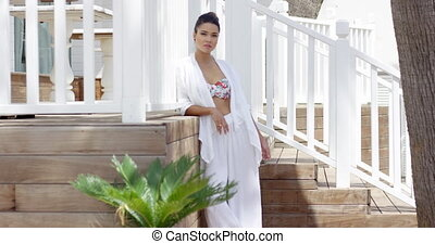 Serious woman standing near wooden stairs