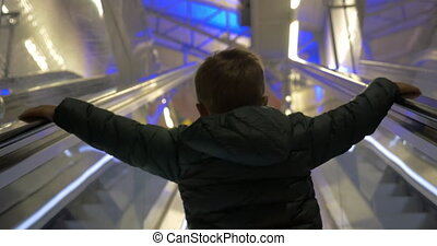 Child getting upstairs on escalator - Back view of a little...