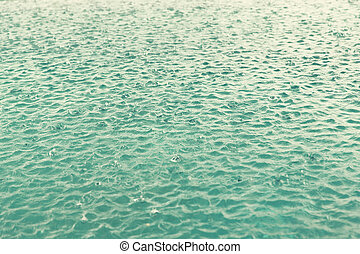 water surface with raindrops at rainy day - weather, rain,...