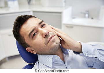 man having toothache and sitting on dental chair - people,...
