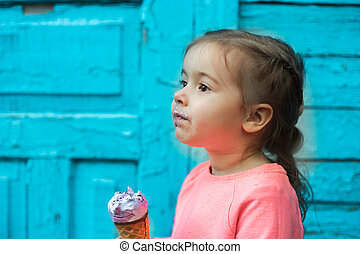 little girl eats ice cream on a beautiful wooden background