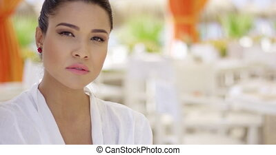 Sultry looking woman at empty outdoor restaurant -...