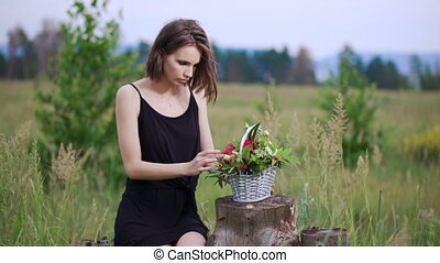 Close up profile portrait of a beautiful and young woman enjoying and smelling a bouquet of flowers