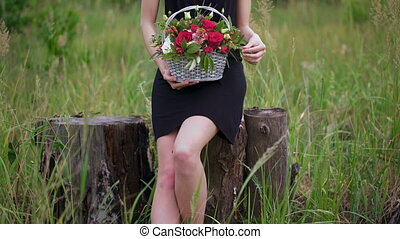 Portrait of a beautiful girl with a basket of flowers in...