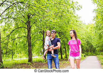 Happy young family walking down the road outside in green...