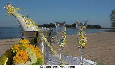 Champagne bottle in ice bucket, two glasses and wedding decor on the beach
