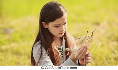 Girl 11 years doing a bouquet of dried grass close up