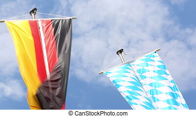 Germany and Bavaria flags in front of blue sky moving in the...