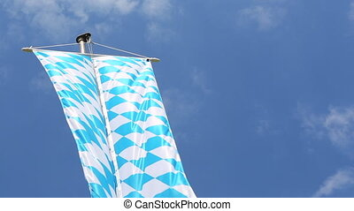 Bavarian flag in front of blue sky moving in the wind
