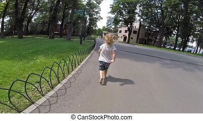 Children run on park - Small child runs on the sidewalk in...