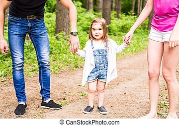 Happy family having fun outdoors and smiling. Funny daughter