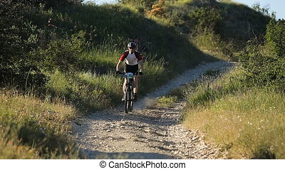 Male cyclist riding on a mountain road on a mountain bike.