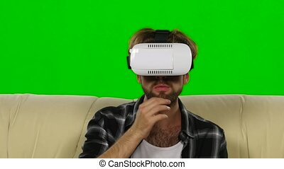 Man in the mask looks VR glasses. Green screen - Young man...