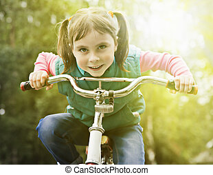 Child on bike driving closeup - Young girl is cycling into...