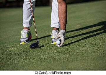 golf player placing ball on tee