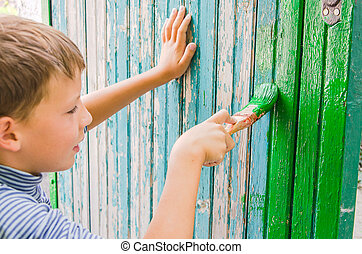 teen paints fence by green color