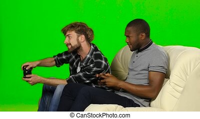 Men play on consoles with wireless joysticks Green screen -...