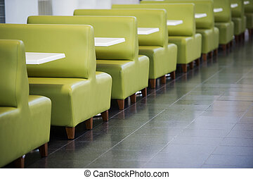 Interior of restaurant zone food court with green sofas and...