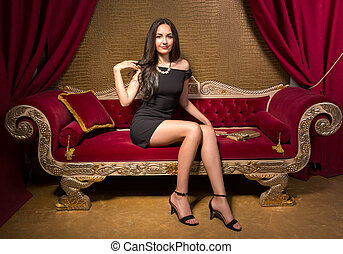 Young beautiful woman in black little dress sitting on a red...
