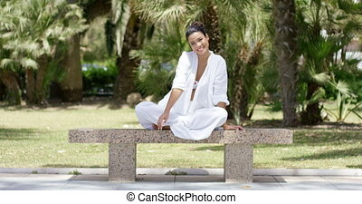 Smiling female sitting by herself on granite bench -...