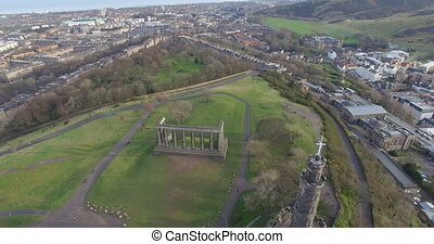 Aerial: View of Edinburgh city over Calton Hill in Scotland