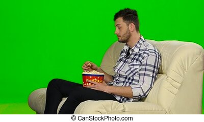 Man watching TV and smiling. Green screen