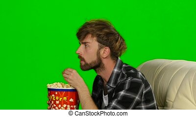 Guy emotional watching a movie and eating popcorn. Green...