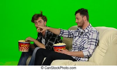 Men on the couch watching a movie and eating popcorn. Green...