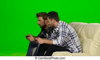 Men play on the console in the same team. Green screen - Men...