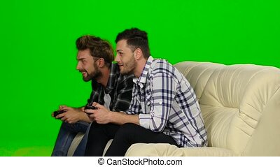 Two guys playing video games with wireless control pad....
