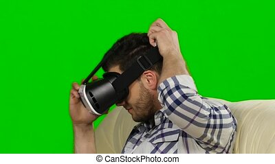 Guy watches the plot of mask of virtual reality. Green...