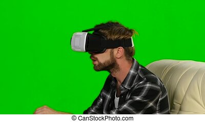 Young man in a VR mask something catches hands. Green screen...