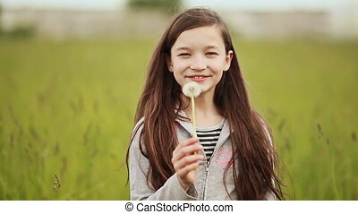 The little 11 year old girl blowing the dandelion.