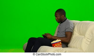 Man lost the game on the console and upset. Green screen