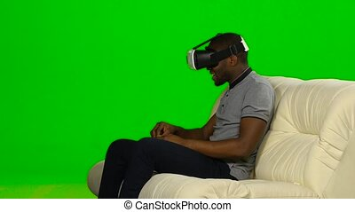 Man watching movie in VR the mask. Green screen
