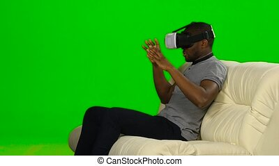 Man in awe of the movie the mask of virtual reality. Green screen