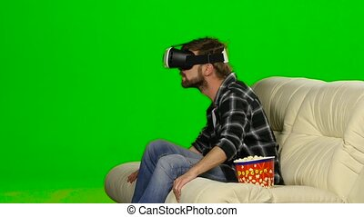 Man in VR mask watching a movie and eating popcorn Green...