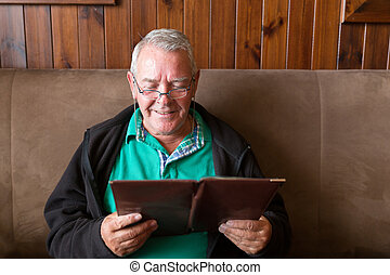 Senior man reading a restaurant menu - Senior man smiling...