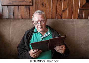 Sober senior man reading a restaurant menu - Sober senior...