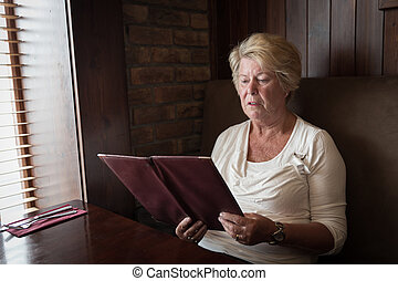 Sober senior woman reading a restaurant menu ready to order...