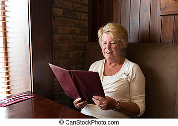 Senior woman reading a restaurant menu - Senior woman...